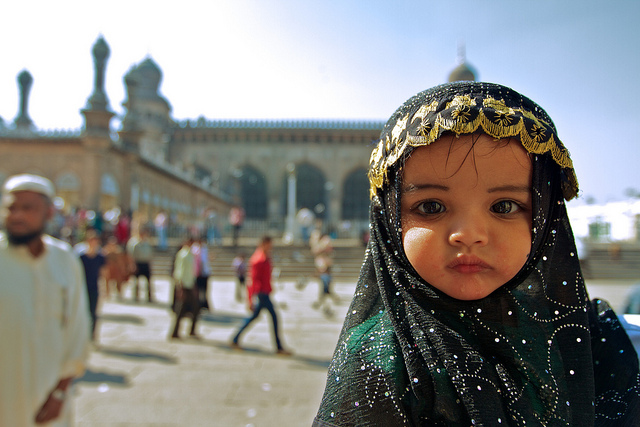 A young girl going to mosque in the Muslim majority city of Hyderabad, dressed in a traditional Hijab. Whilst it is uncommon for children so young to wear Hijabs, on special occasions, such as Friday prayers, they are worn. Photo Credit: --A baby at a mosque by Johanan Ottensooser